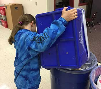 Alki student emptying recycling bin