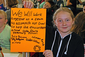 student holding green pledge sign