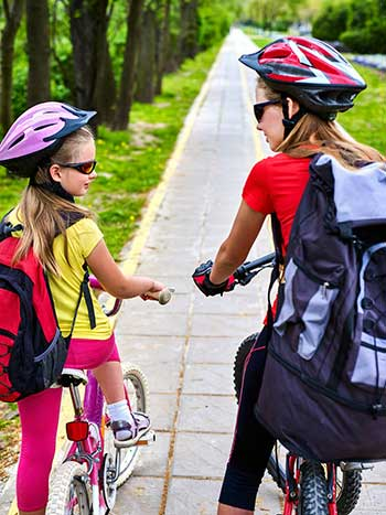 teen and younger girl riding bikes to school